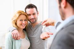 l-agente-immobiliare-consegna-le-chiavi-di-nuova-casa-alle-giovani-coppie-50887626