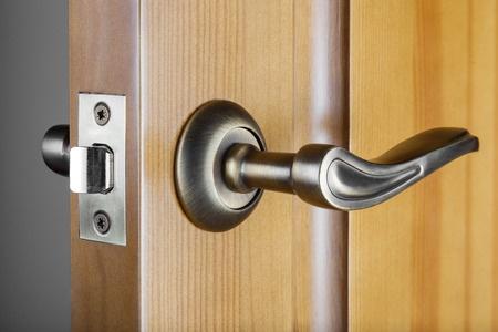 35455975 - slightly opened wooden door with latch handle closeup