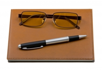 4784727 - daily planner with glasses and pen isolated on white background